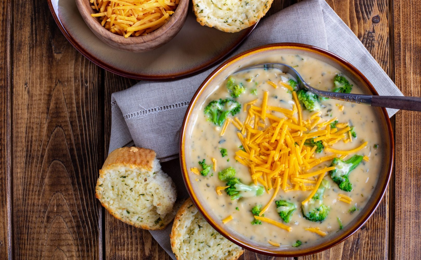 Overhead view of a bowl of creamy broccoli cheddar soup with toasted cheese bread on a wooden table